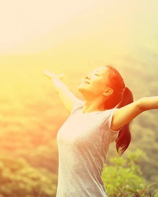 woman reaching out to sun